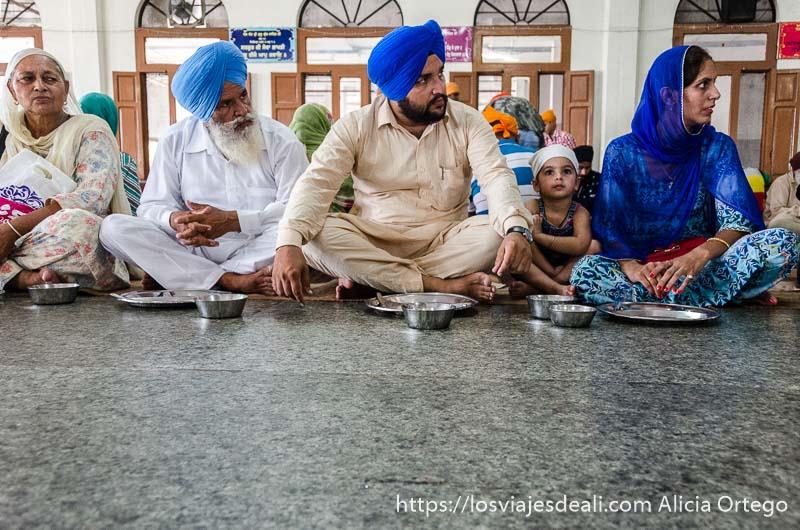 familia comiendo sentados en el suelo en el templo dorado de los sijs