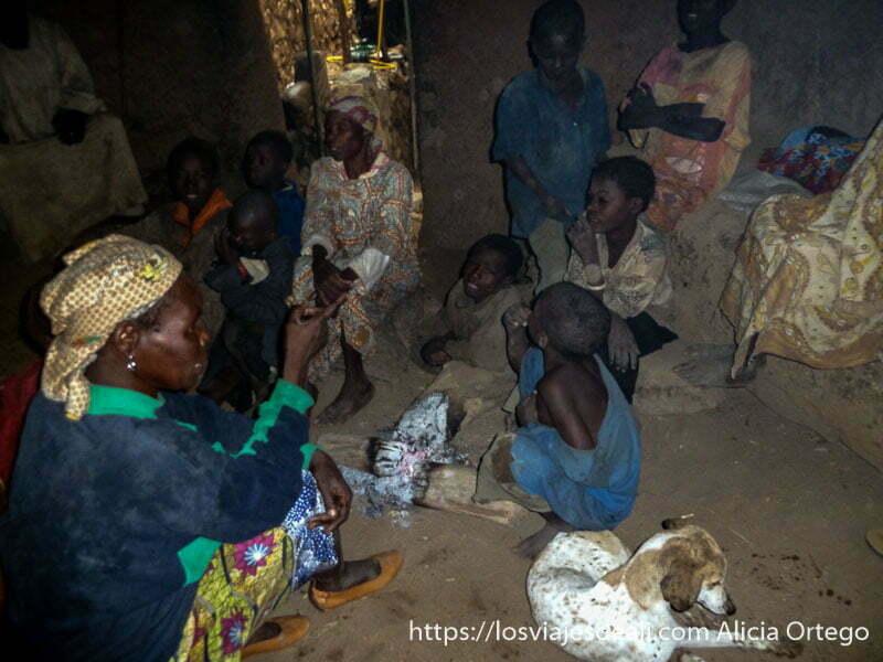 interior de vivienda llena de mujeres y niños alrededor del fuego y un perro trekking en los montes mandara de camerún