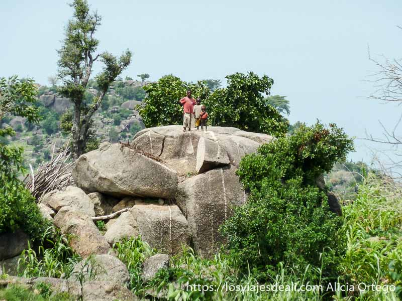 tres niños pequeños sobre una gran roca mirándonos trekking en el monte ziver