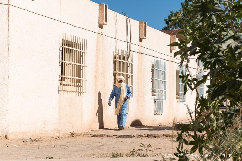 tuareg con gran turbante blanco y túnica azul andando junto al museo de djanet