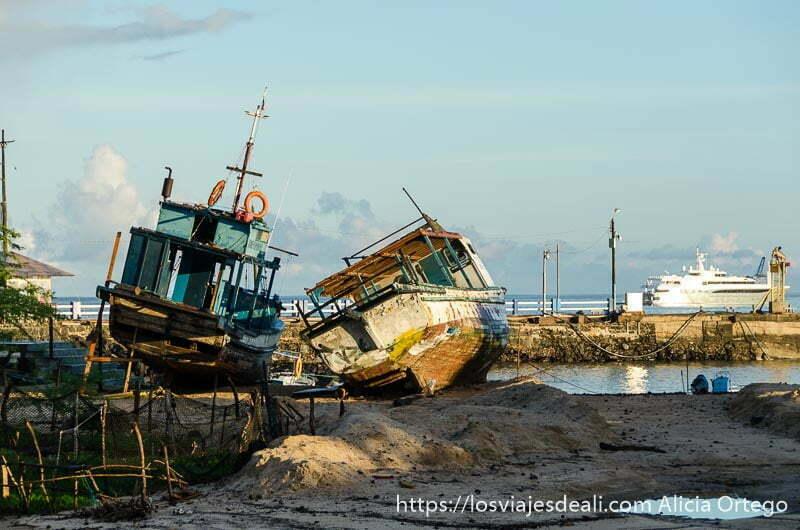 barcos viejos varados y al fondo un yate en el mar vivir en las islas galápagos