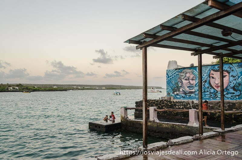 niños bañándose en un muelle junto a muro con grafitis en isla santa cruz galápagos