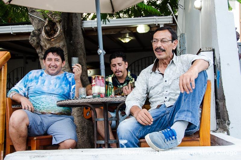 tres hombres bebiendo en una terraza y uno de ellos tocando la guitarra vivir en las islas galápagos