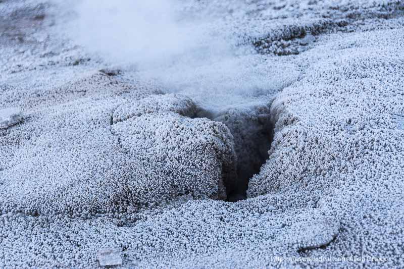 agujero por donde sale vapor en el suelo cubierto de hielo en los geysers del tatio
