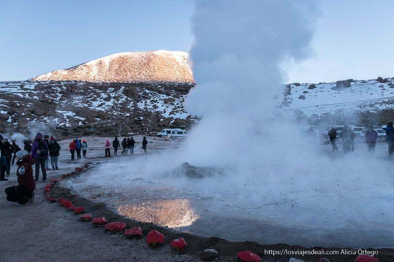 gran fumarola con gente alrededor y montaña iluminada por el sol al fondo geysers del tatio