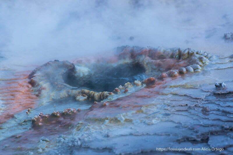 agujero por donde sale vapor y agua con suelo de colores rojos y amarillos geysers del tatio
