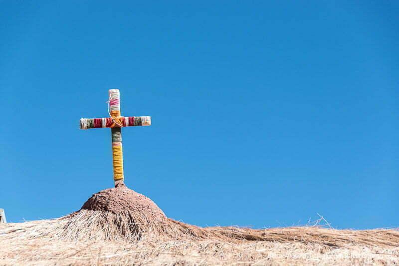 cruz de madera revestida de hilos de colores en el tejado de la iglesia de machuca