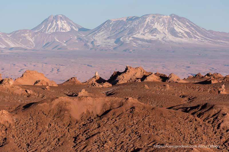 paisaje rugoso con luz anaranjada y volcanes con algo de nieve en el horizonte en el valle de la luna