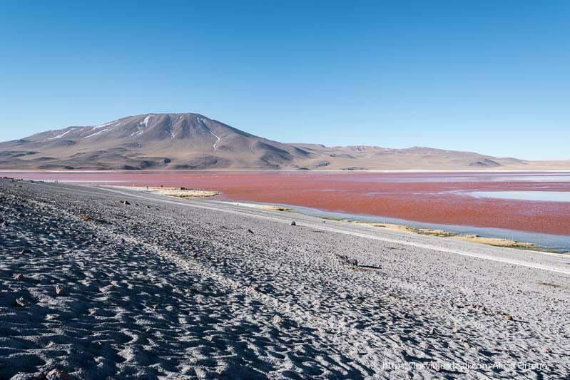 ladera de arena y laguna colorada con volcán al fondo bolivia