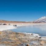 laguna blanca de bolivia con agua azul claro que refleja volcán nevado, orilla blanca con personas andando y coches 4x4 parados al lado consejos para evitar el mal de altura