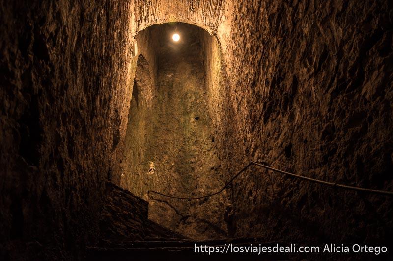 escaleras de subida dentro de las minas con una bombilla encendida escapada a ronda