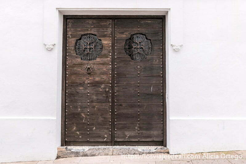 puerta de madera con tachones de hierro en un muro blanco escapada a ronda