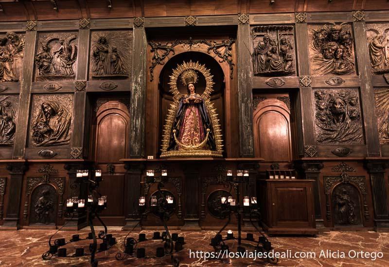 retablo de madera oscura con escenas esculpidas y virgen en el centro escapada a ronda
