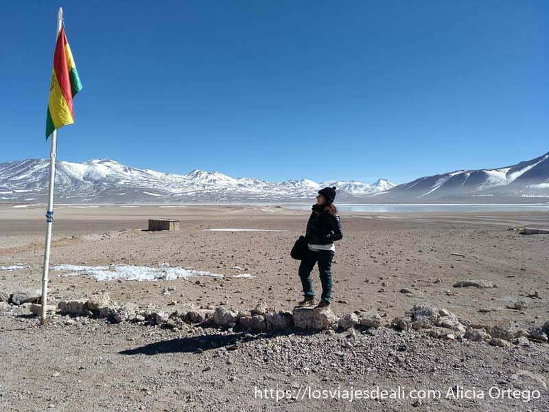 posando con la bandera de bolivia y detrás la laguna blanca y volcanes nevados
