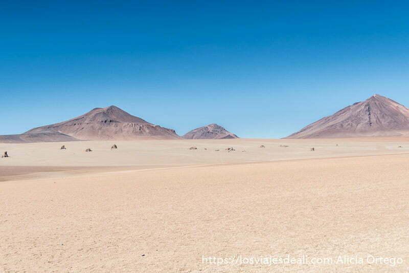 desierto de dalí salpicado de rocas y con volcanes al fondo en reserva nacional de fauna andina eduardo avaroa