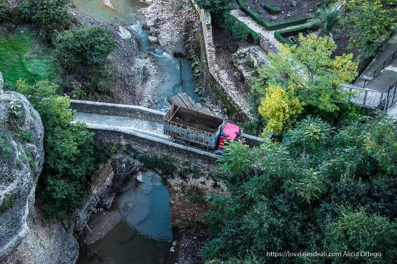 puente viejo con un camión cruzándolo y el río guadalevín debajo escapada a ronda