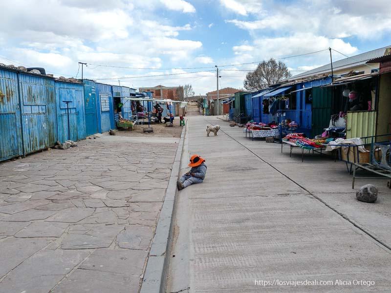 calle del pueblo de san cristóbal con una niña sentada en la acera
