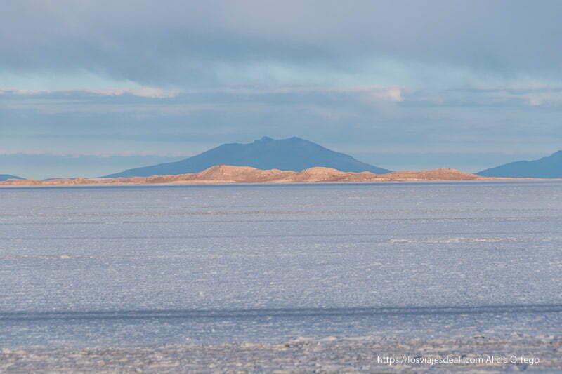 salar de uyuni con volcanes al fondo y línea de montañas naranjas por el sol