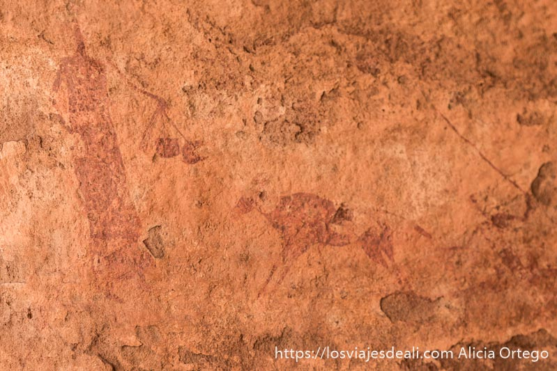 pintura rupestre de mujer llevando dos cacharros en la mano y una vaca pequeña al lado