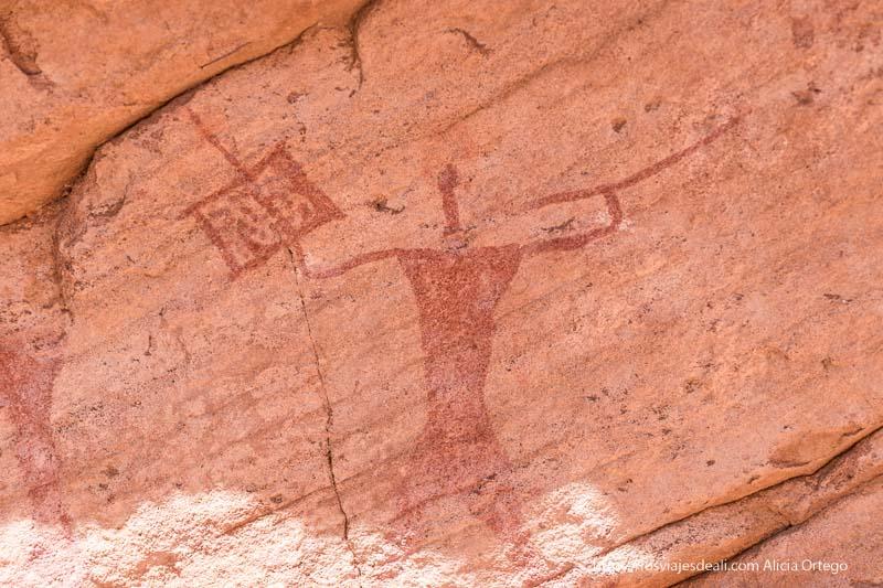 guerrero con lanza y escudo pintado en rojo en una pared en el tassili