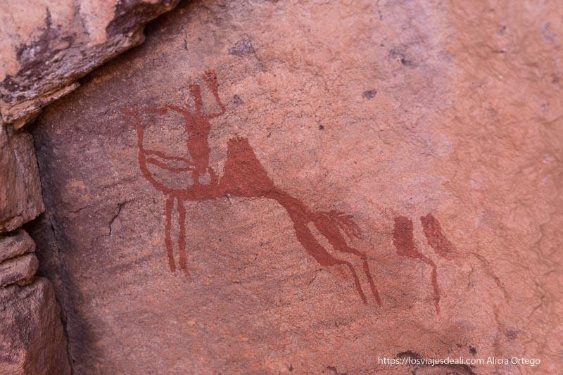 pintura rupestre de color rojo de un hombre montado en camello en el sahara