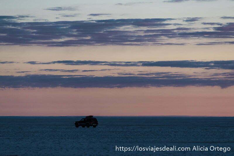coche circulando en el salar de uyuni con cielo rojizo por amanecer