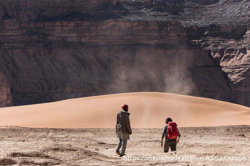 guía tuareg con turista con mochila andando por el tadrart consejos para viajar a argelia