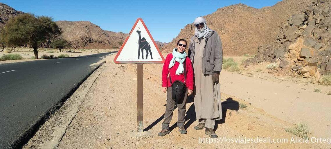 foto de mi misma con moussa junto a una señal de tráfico con un camello consejos para viajar a argelia