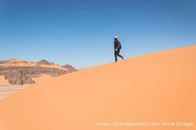turista andando por duna con cielo azul detrás consejos para viajar a argelia