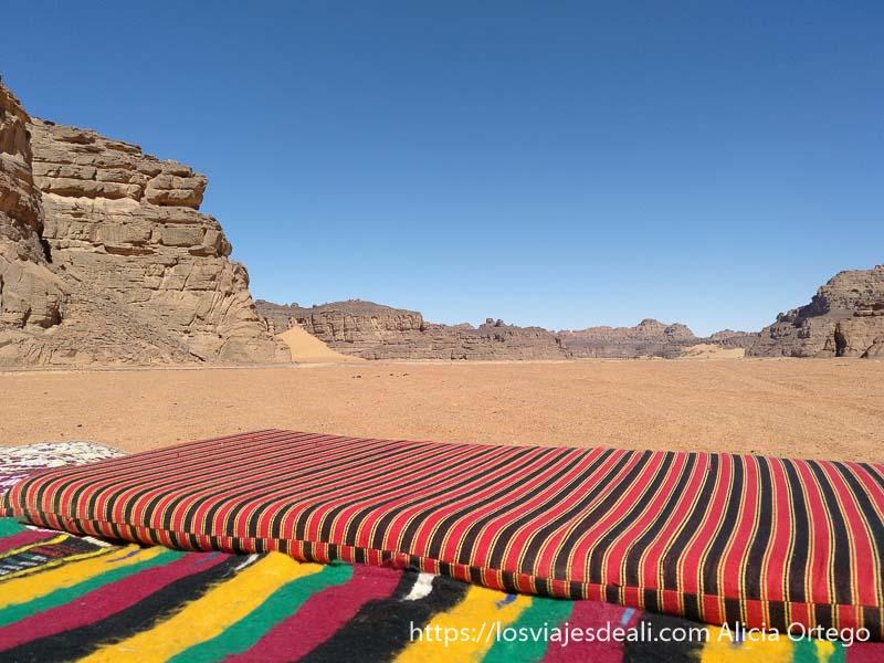 colchonetas y mantas a rayas de colores sobre la arena con grandes rocas al fondo y cielo azul en el tassili sahara