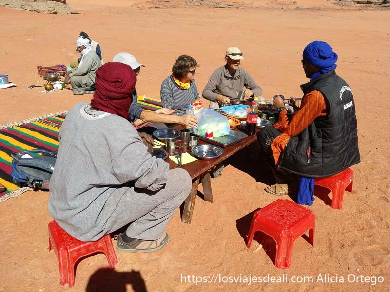 mesa con sillas y grupo sentado a la mesa con los guías