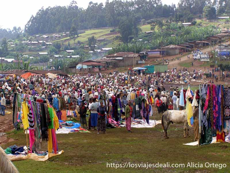 mercado dorze lleno de gente con puestos de ropa y ladera de montaña verde