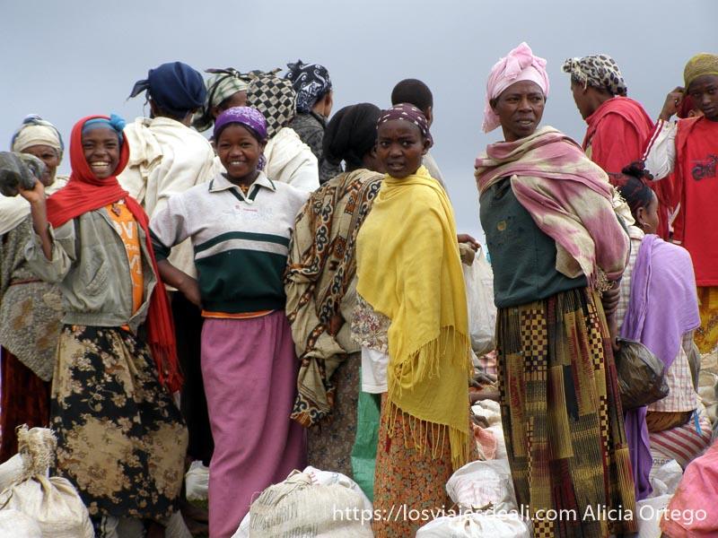 chicas mirando a la cámara y riéndose entre sacos de ayuda humanitaria en el mercado dorze de etiopía
