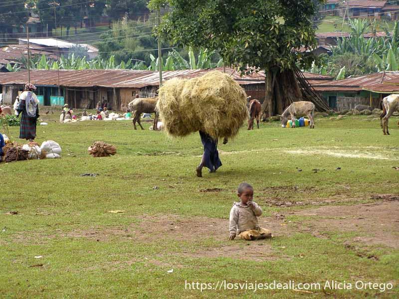 mujer llevando gran montón de hierba sobre los hombros y bebé sentado en la hierba