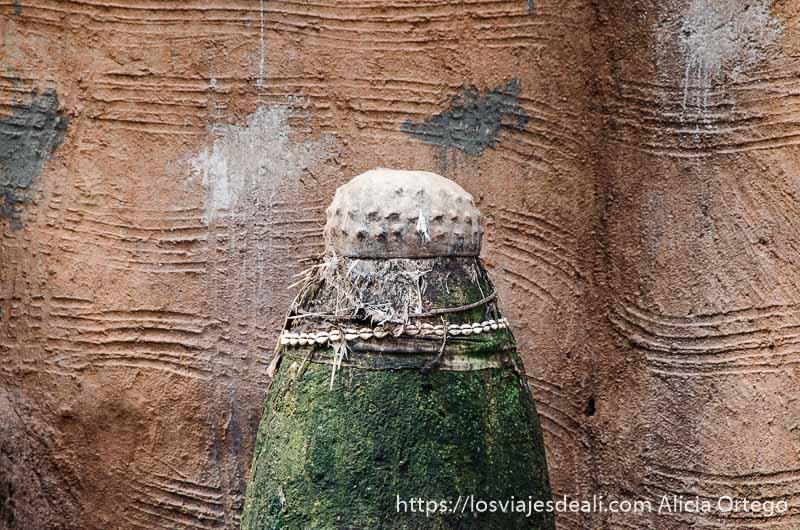 fetiche hecho con figura cilíndrica de barro y olla de cerámica en parte superior boca abajo tribus de benin