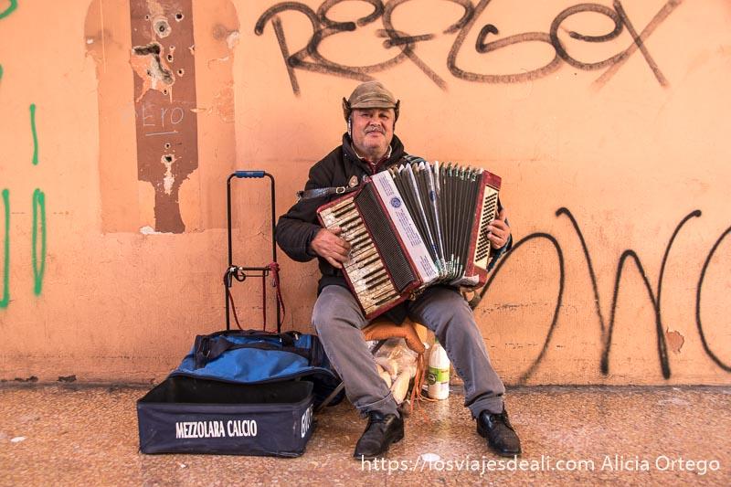 señor que toca el acordeón en la calle pidiendo dinero
