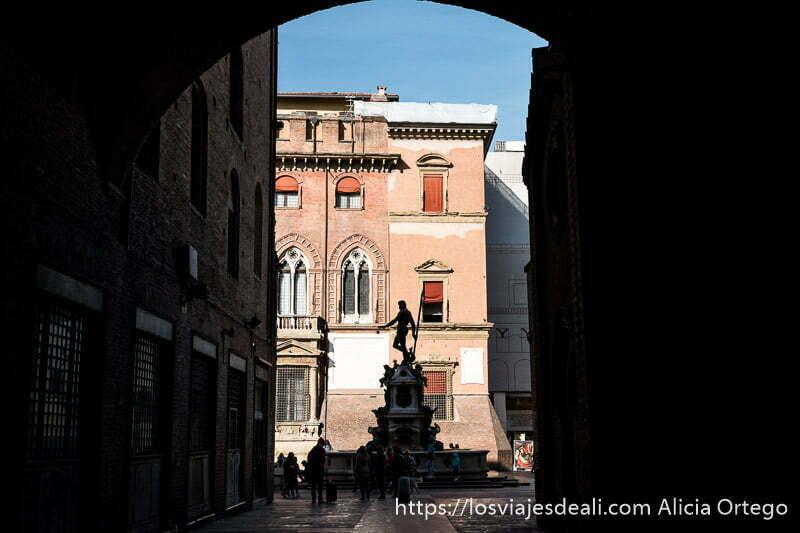 estatua de neptuno a contraluz vista a través de un arco