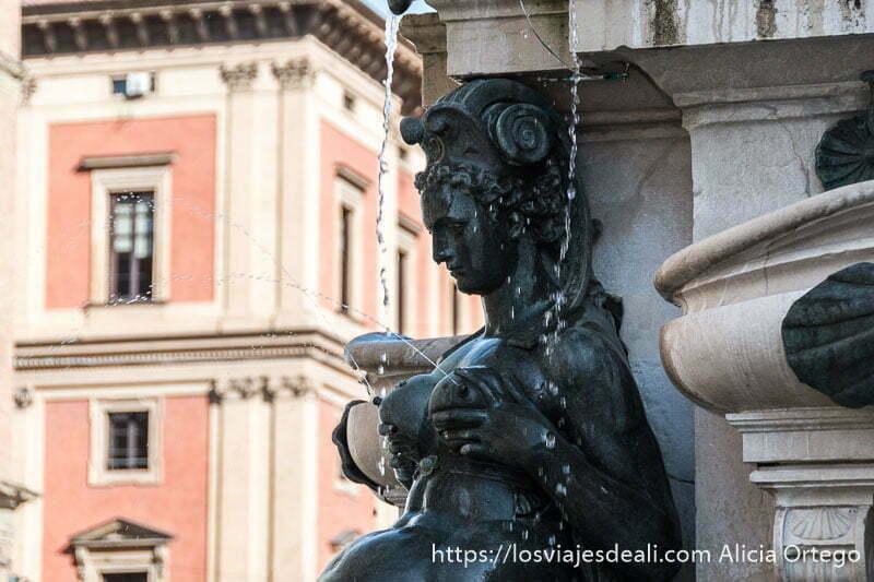estatua de fuente de neptuno de sirena cogiéndose los pechos con las manos y saliendo agua por los pezones
