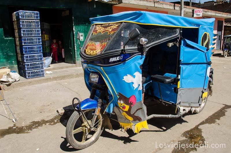 motocarro tipo rickshaw con cubierta de plástico azul con dibujos de la Warner