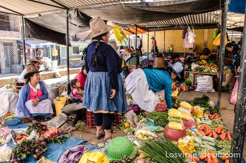 mujeres con sombreros y faldas en puestos de verduras