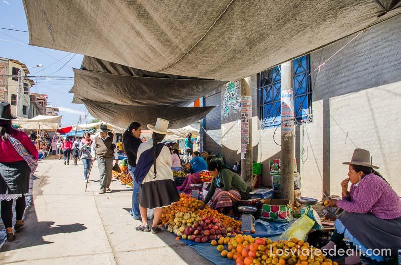 puestos de frutas alineados bajo toldos en un pueblo del callejón de huaylas