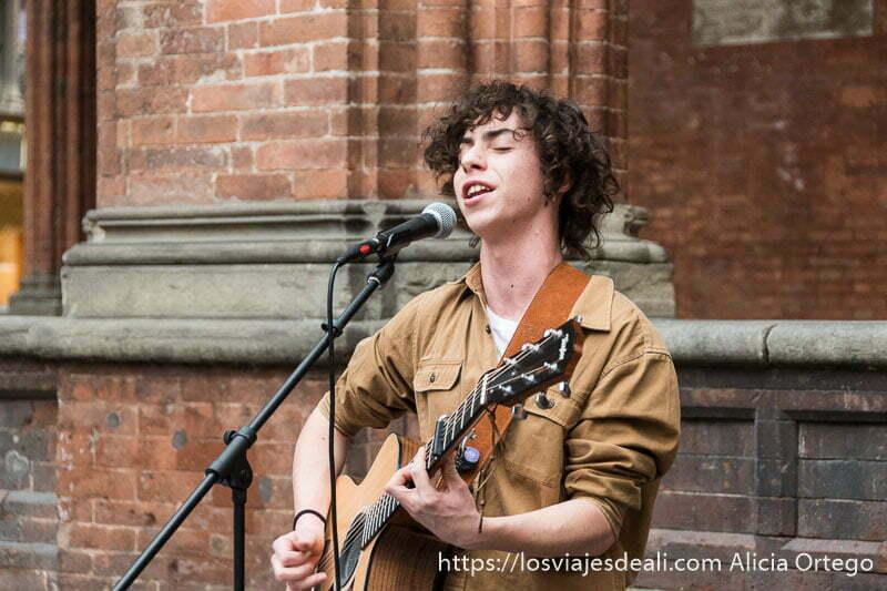 chico joven cantando con su guitarra ante un micrófono en el centro de bolonia