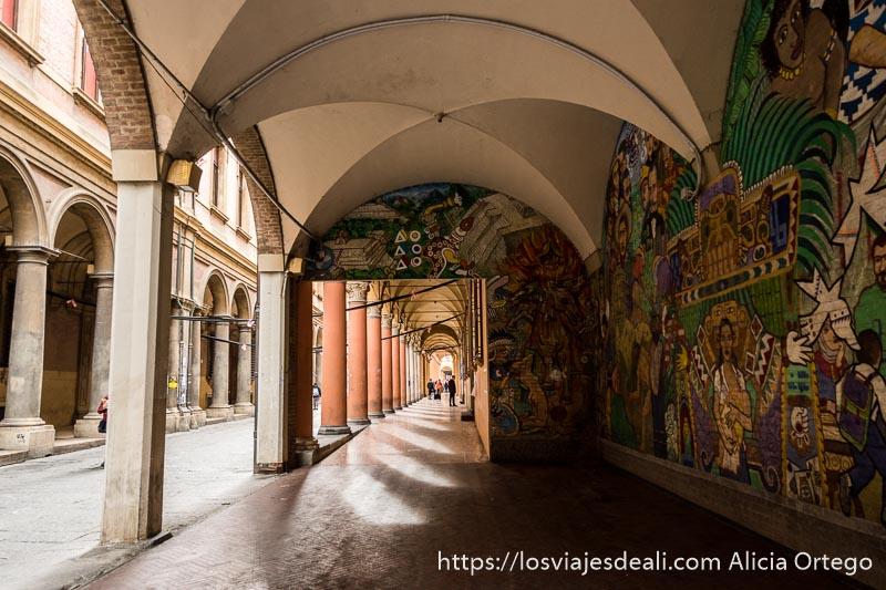 calle porticada con gran mural de símbolos y figuras indígenas