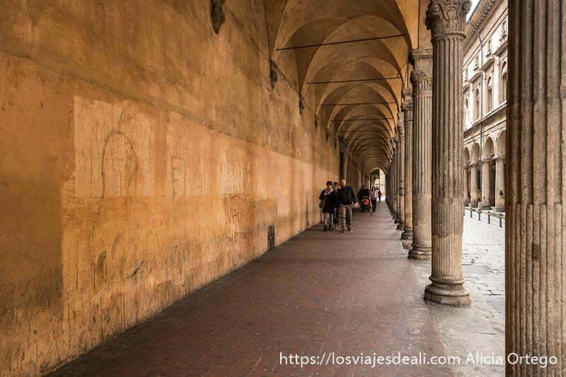 calle porticada con columnas de capiteles corintios en callejear por bolonia