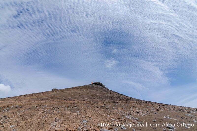 cumbre de isla bartolomé con un faro naranja y muchas nubes en el cielo