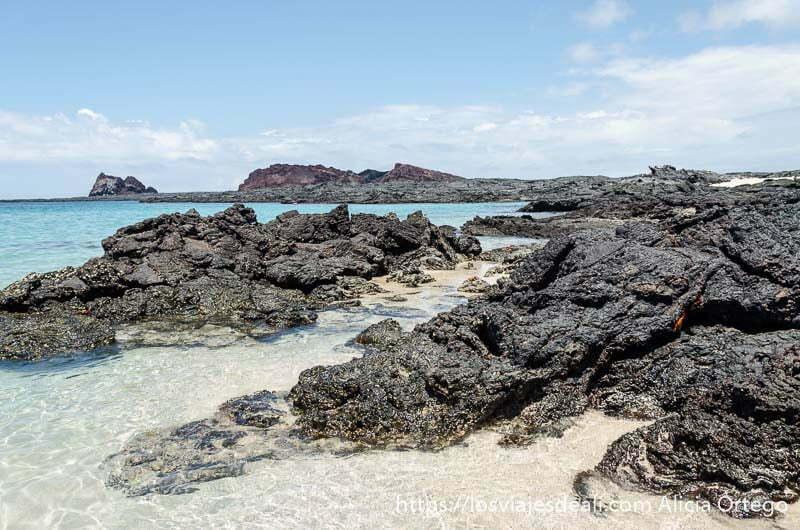 rocas volcánicas que terminan en el mar entre arena blanca en la isla bartolomé