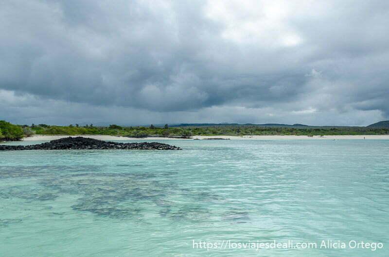 playa de agua transparente con rocas volcánicas y grandes nubes de tormenta
