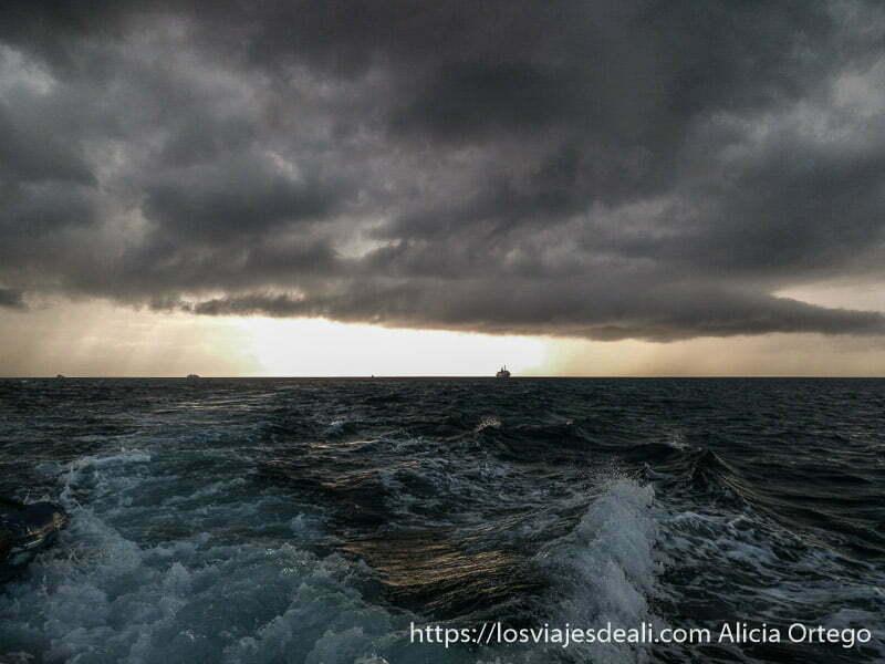 gran tormenta en el mar con barco en el horizonte recortándose con la luz del sol