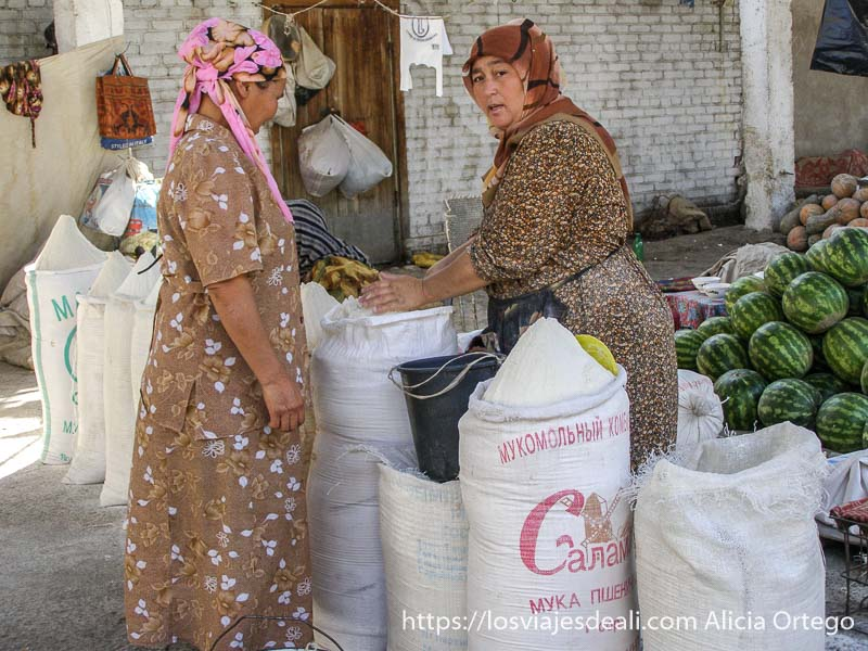 una mujer cogiendo harina de una gran saco para vendérsela a una clienta en el valle de fergana