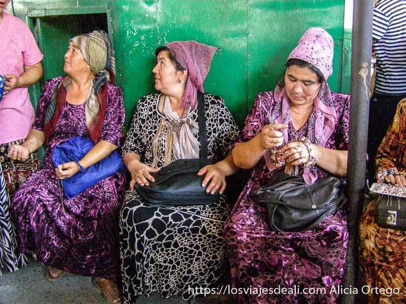 tres mujeres vendedoras de joyas sentadas en sillas todas con vestidos estampados y pañuelos en la cabeza